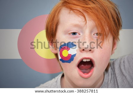 redhead fan boy with colorado state flag painted on his face. on the colorado state flag background - stock photo