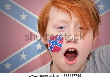 redhead fan boy with  confederate flag painted on his face.  - stock photo