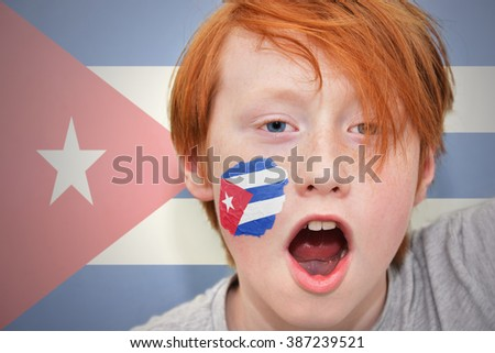 redhead fan boy with cuban flag painted on his face. - stock photo