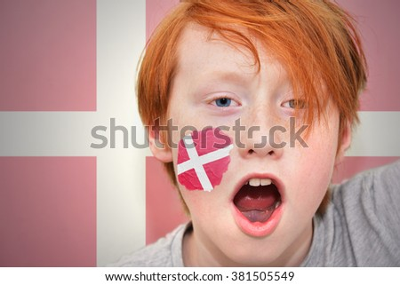 redhead fan boy with danish flag painted on his face. on the  danish flag background - stock photo