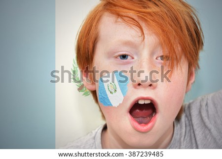 redhead fan boy with guatemalan flag painted on his face.  - stock photo