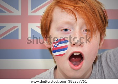redhead fan boy with hawaii state flag painted on his face.  - stock photo