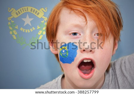 redhead fan boy with nevada state flag painted on his face.  - stock photo