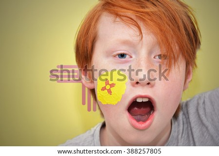 redhead fan boy with new mexico state flag painted on his face. - stock photo