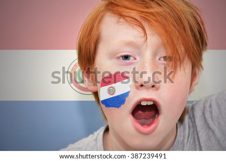 redhead fan boy with paraguayan flag painted on his face.  - stock photo
