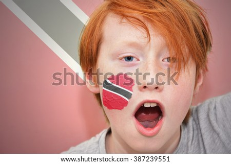 redhead fan boy with trinidad and tobago flag painted on his face.  - stock photo