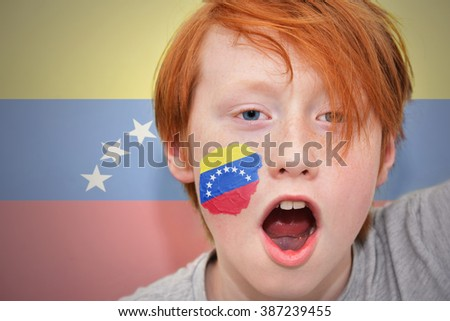 redhead fan boy with venezuelan flag painted on his face.  - stock photo
