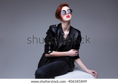 Redhead fashion model in sunglasses and black leather jacket. Pixie cut hairstyle. Punk, rock style fashion - stock photo