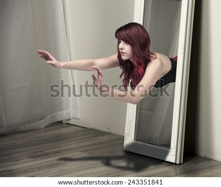 Redhead girl floating out of a mirror