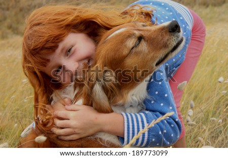 Redhead girl hugging red-haired dog in a grassy field  - stock photo