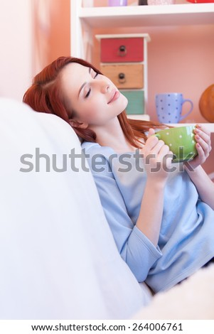Redhead girl in blue blouse with green cup sitting on sofa at home - stock photo