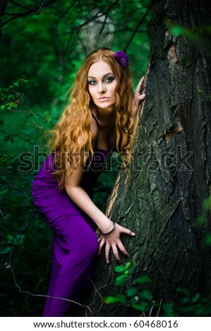 Redhead girl in forest in purple dress - stock photo