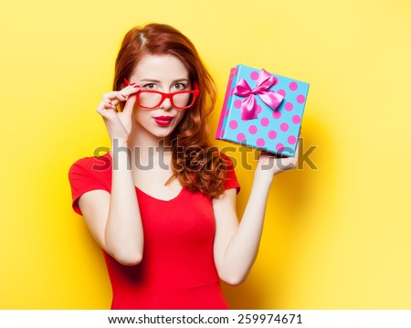 Redhead girl in red dress with glasses and gift box on yellow background - stock photo