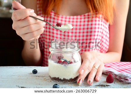 Redhead girl in red morning dress eating creamy dessert in jar with brownies and yogurt topped with fresh raspberries and blueberries, bright colorful image. Clean eating - stock photo