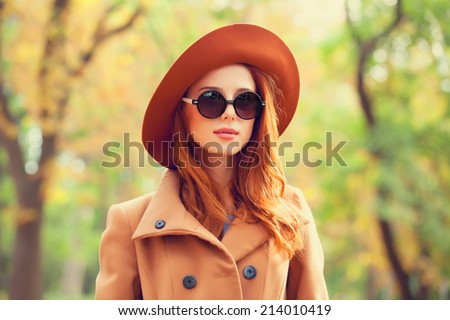 Redhead girl in sunglasses and hat in the autumn park. - stock photo