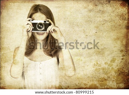 Redhead girl in white dress with vintage camera. Studio shot. - stock photo