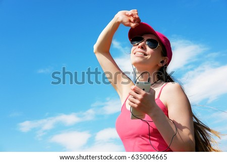 redhead girl is listening to music during jog in summer, copy space