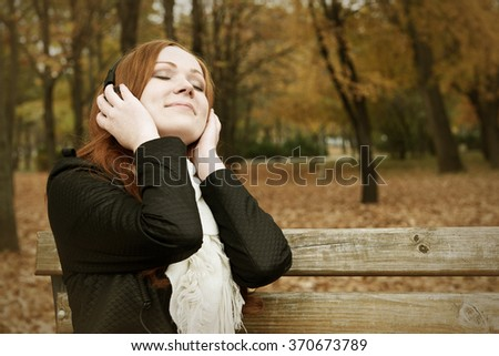 redhead girl listen music on headphones and relaxing in city park, fall season - stock photo