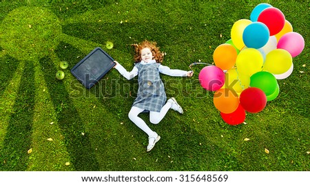 Redhead girl lying on the green grass in park in sunset light. High top view. Happy childhood, back to school, education concept. - stock photo