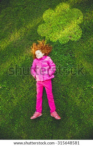 Redhead girl lying on the green grass in park under lighting cloud in sunset light. High top view, happy childhood, active springtime or autumn  holidays. - stock photo
