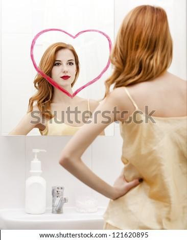 Redhead girl near mirror with heart it in bathroom. - stock photo
