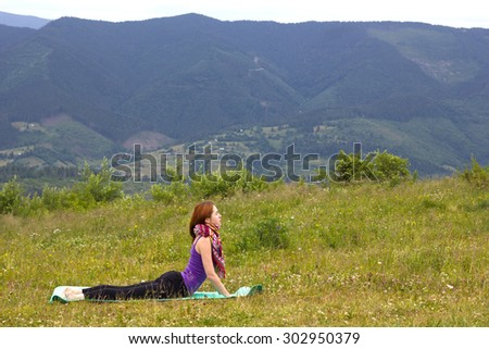 redhead girl practices yoga in the mountains