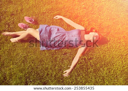 redhead girl relaxing lying on the grass. woman relaxation outdoor - stock photo