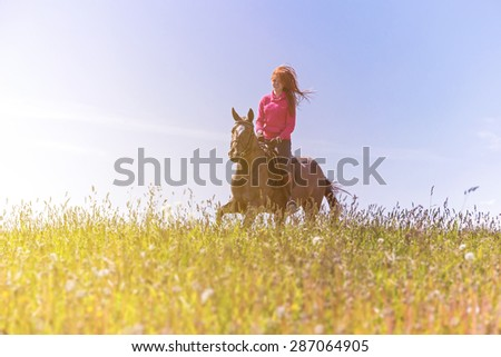 Redhead girl riding horse at summer day - stock photo
