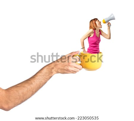 Redhead girl shouting with a megaphone inside cup of coffee - stock photo