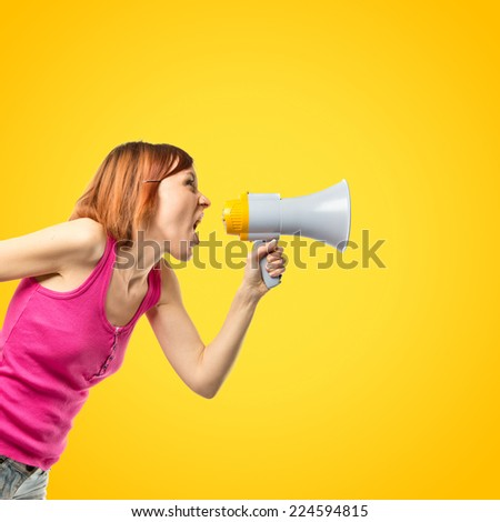 Redhead girl shouting with a megaphone over yellow background  - stock photo