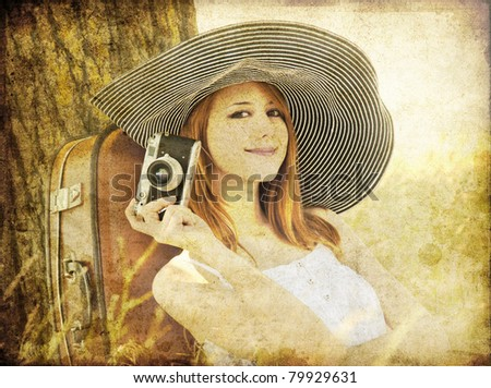 Redhead girl sitting near tree with camera. Photo in old image style. - stock photo