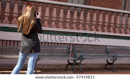 Redhead girl taking a shot of an old building with a digital SLR camera.