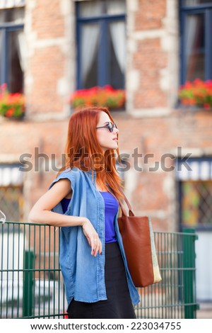 Redhead girl waiting near fence on the street