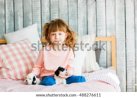 Redhead girl with a cocker spaniel puppies