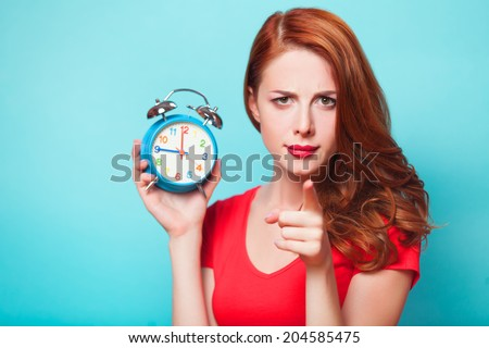 Redhead girl with alarm clock on blue background. - stock photo