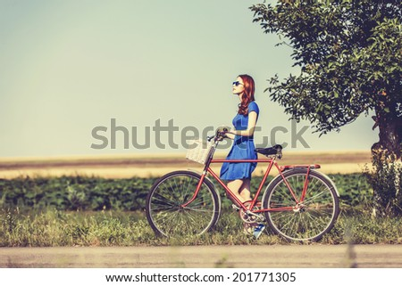 Redhead girl with bicycle on country road. - stock photo