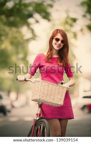 Redhead girl with bike on the street