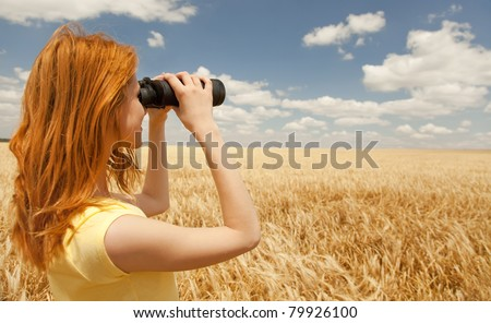 Redhead girl with binocular at wheat field. - stock photo