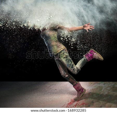 Redhead girl with colored powder exploding around her head and into the background. - stock photo