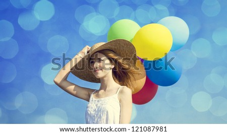Redhead girl with colour balloons. Photo with bokeh at background.