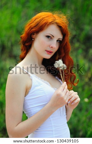 Redhead girl with dandelions, outdoor. - stock photo