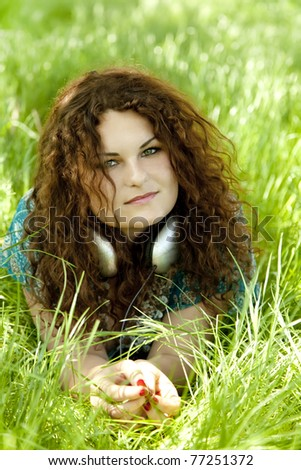 Redhead girl with headphone at green grass. - stock photo