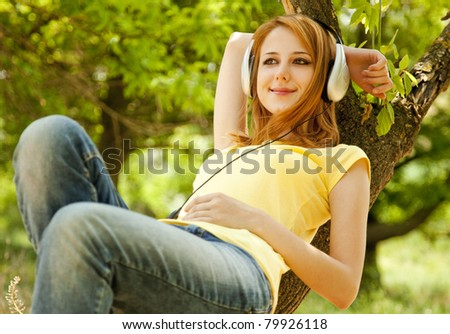 Redhead girl with headphones lie over tree at garden.