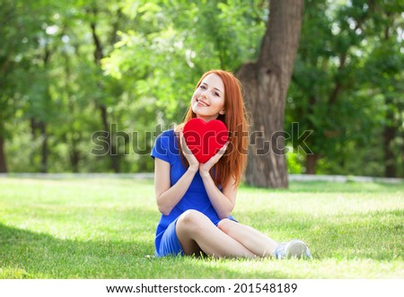 Redhead girl with heart shape in the park. - stock photo