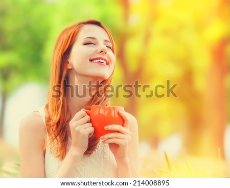 Redhead girl with orange cup at outdoor - stock photo