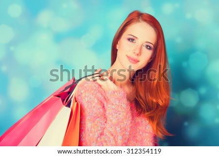 Redhead girl with shopping bags on blue background. - stock photo