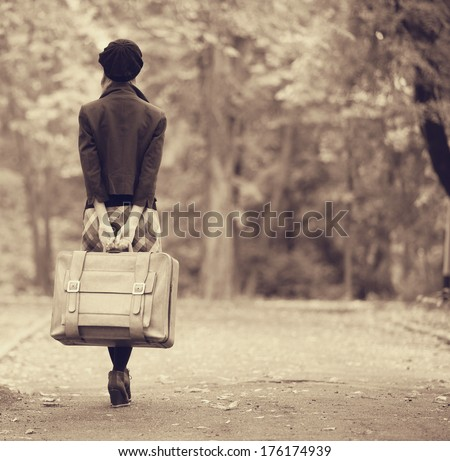 Redhead girl with suitcase at autumn outdoor. Photo in old color image style. - stock photo