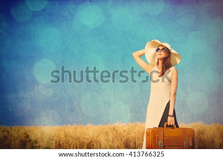 Redhead girl with suitcase at countryside road near wheat field. - stock photo