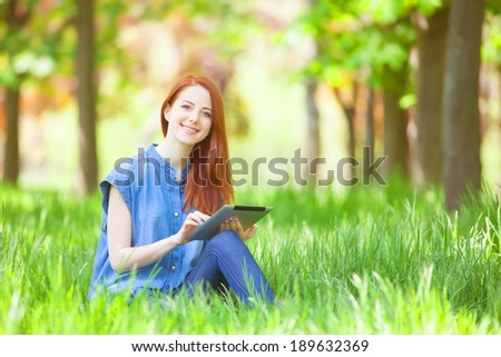 Redhead girl with talet in the park - stock photo