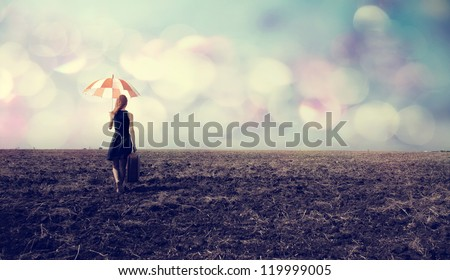 Redhead girl with umbrella and suitcase at windy field - stock photo